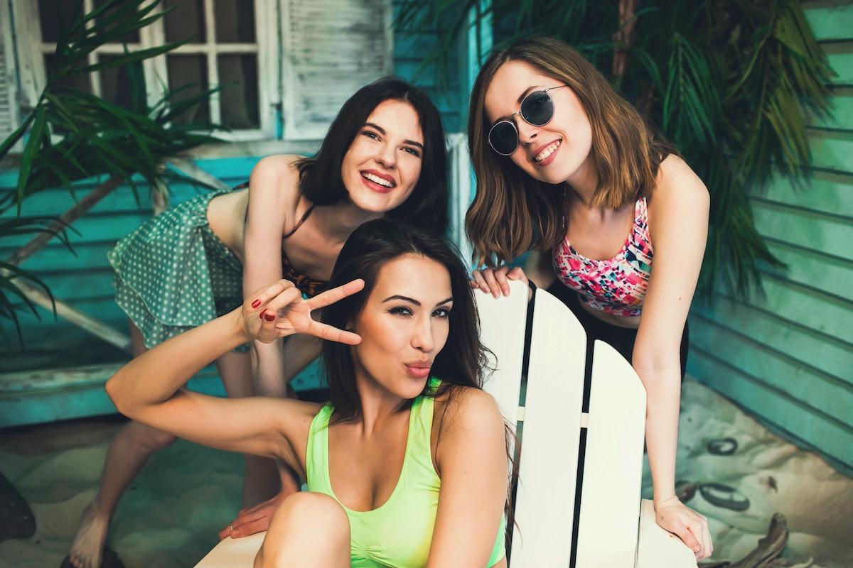 Three beautiful female friends make fun and selfie at beach house neae ocean side at sunset