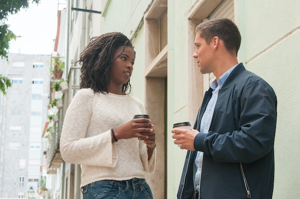 Serious black girl arguing with Caucasian boyfriend outdoors. Mix raced couple standing at European apartment building, drinking takeaway coffee and talking. Millennials concept