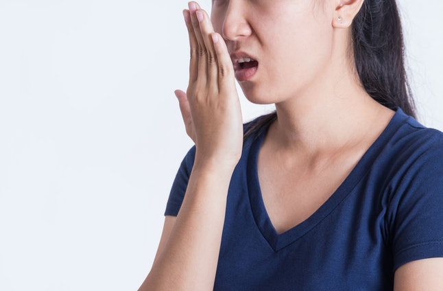 Asian woman checking her breath with her hand on white background.