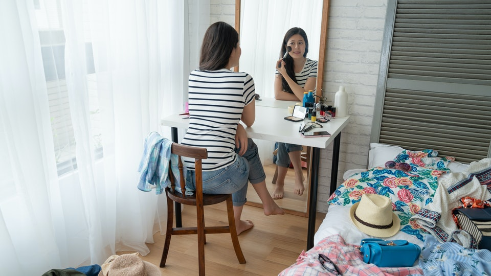 back view young beautiful woman making make up near mirror at dressing table. smiling asian female sitting in bright cozy bedroom with messy cloth on bed home. get ready packing for summer vacation