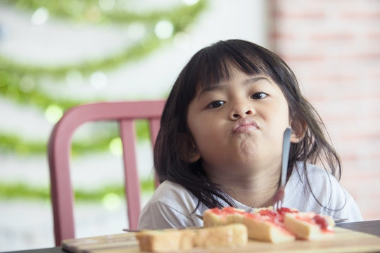 cute baby eating boring food,Asian baby bored looking face looking at her breakfast,Children with bread
