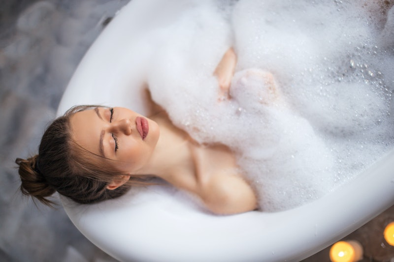 Relaxed young woman laying in bathtub. enjoyment concept