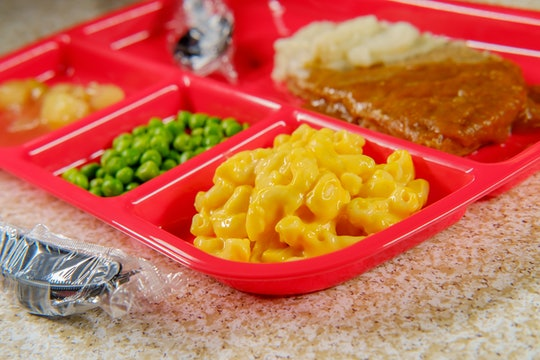 Grade school lunch salisbury steak on tray with peas macaroni and cheese and apple sauce