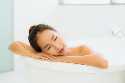 Portrait beautiful young asian woman relaxing bathtub in bathroom interior