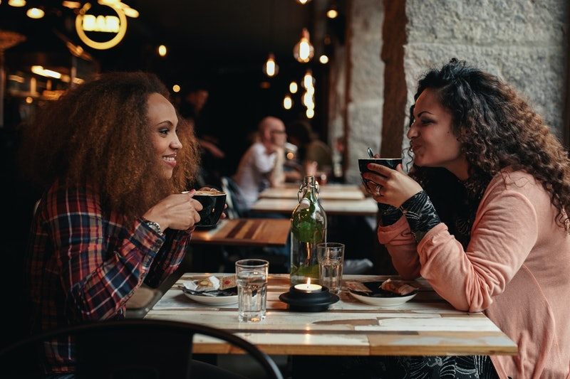 Side view portrait of two young women talking and drinking coffee in a cafe. Female friends in a restaurant.