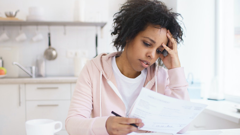 Upset african american female sitting at kitchen table with laptop, dealing with financial stress and pressure because of mortgage debt, worrying a lot or feeling anxious over money