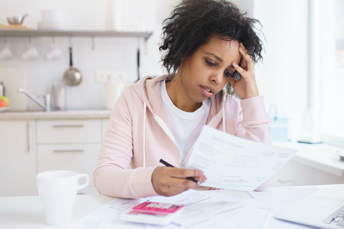 Upset african american female sitting at kitchen table with laptop, dealing with financial stress an...