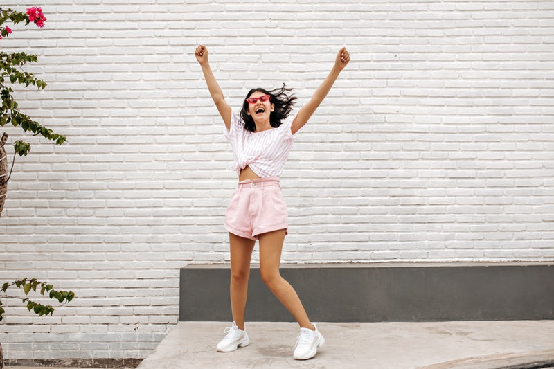 Debonair girl jumping with hands up on street. Outdoor shot of blithesome female model having fun in summer.