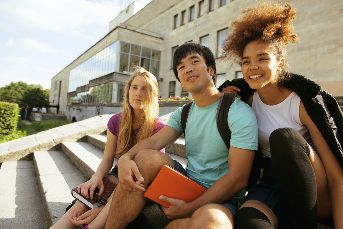 cute group of teenages at the building of university with books huggings, smiling, back to school