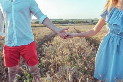 A guy with a girl in the summer goes on a wheat field, holding each other hands. Close-up summer in the countryside. The concept of happy relationships and strong love in marriage.