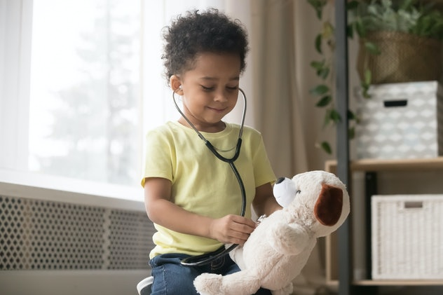 Cute little toddler african american boy playing funny game as doctor holding stethoscope listening ...