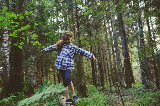 happy kid girl exploring summer forest, traveling on vacation. Teaching kids to love nature. Earth day concept.
