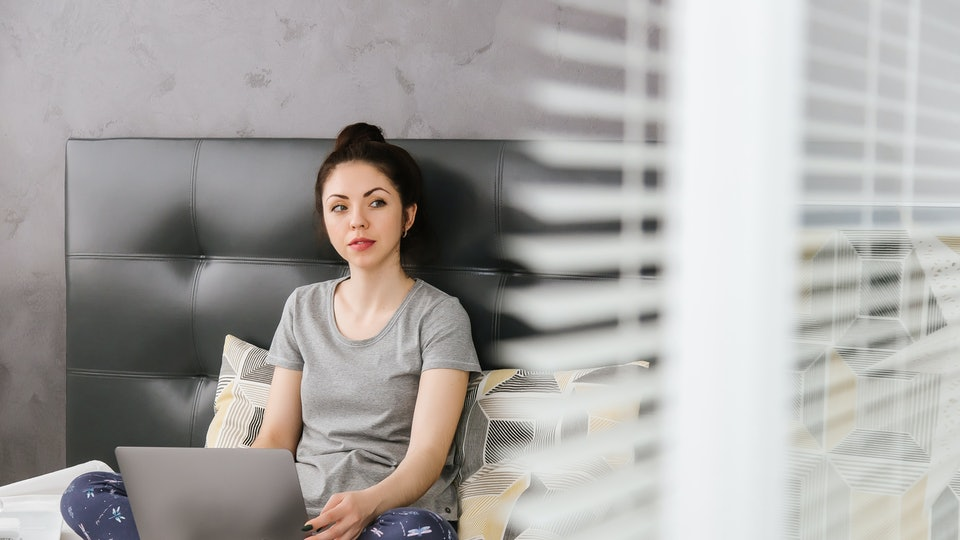 A beautiful young Asian woman in home clothes and glasses is sitting on the gray bed and holding a laptop, notebook. remote work