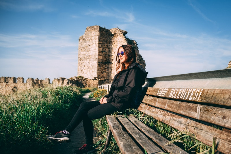 Girl with sunglasses sitting on a bench sunbathing on sinop