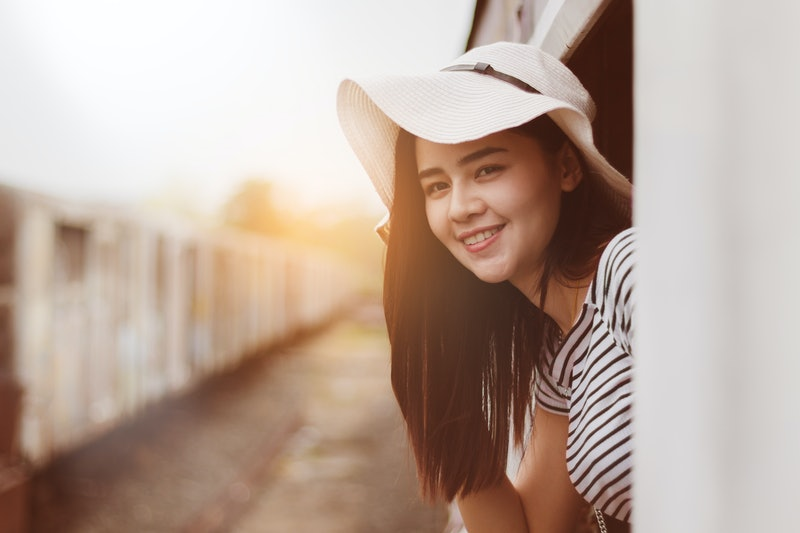 Asia woman travelling by train alone with fun and happy.