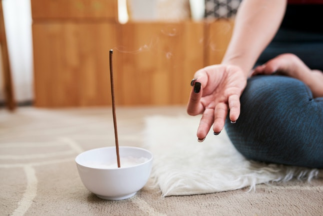 Bowl with scented aroma stick next to meditating young woman