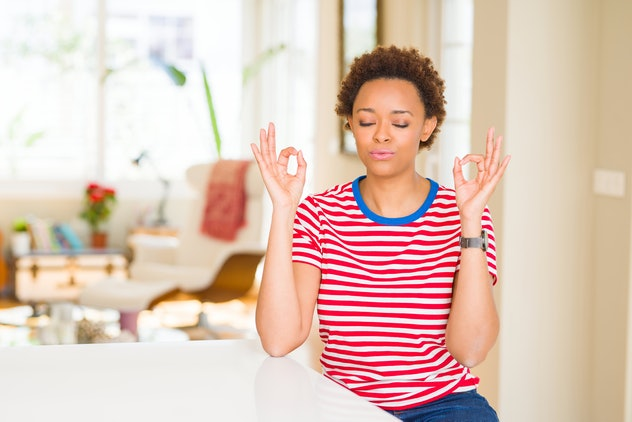 Young beautiful african american woman at home relax and smiling with eyes closed doing meditation gesture with fingers. Yoga concept.