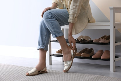 Woman putting on shoes indoors, closeup. Stylish hallway interior