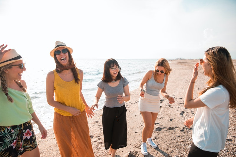Group of women friends having fun and dancing on the beach. Holiday concept