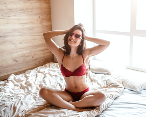 Seductive young naked dark-haired woman on bed in morning. Sexy hot beautiful brunettte sitting with legs crossed and posing. Smiling. Woman wear red lingerie and red sunglasses.