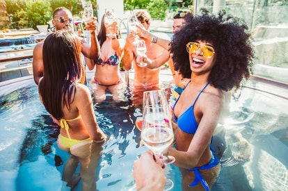 Happy multiracial friends having fun on a pool party on vacation - Luxury vacation concept with young people in summer at hotel resort - Pov view