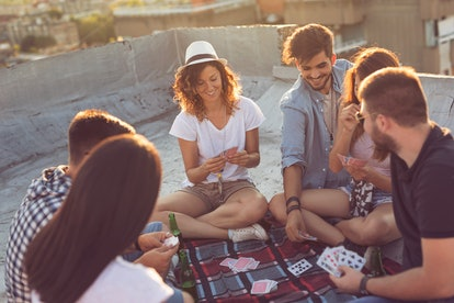 Group of young people sitting on a picnic blanket, having fun while playing cards on the building rooftop. Focus on the girl in the middle