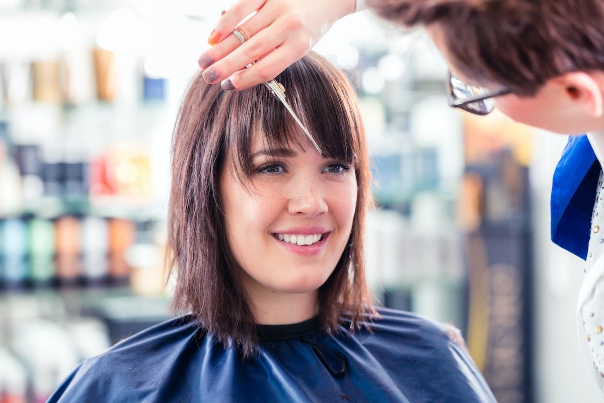 Hairdresser cutting woman hair in shop