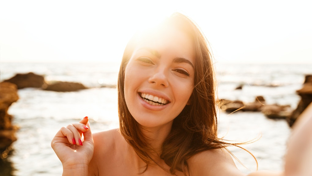 Close up image of happy brunette woman making selfie on beach