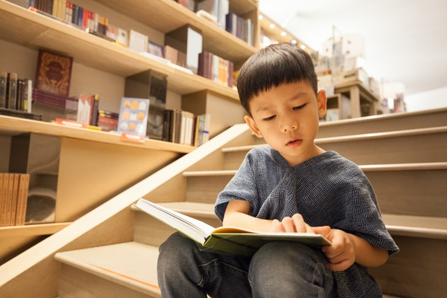 Portrait shot of an Asian pre-school boy sitting on the stairs, reading book in the library paying f...