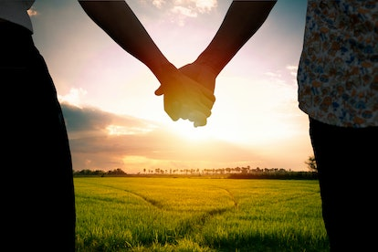 Couple holding hands and Beautiful sunlight on the sky in background.