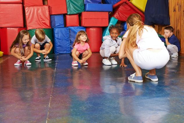 Children doing gymnastics in physical education with nursery teacher in preschool