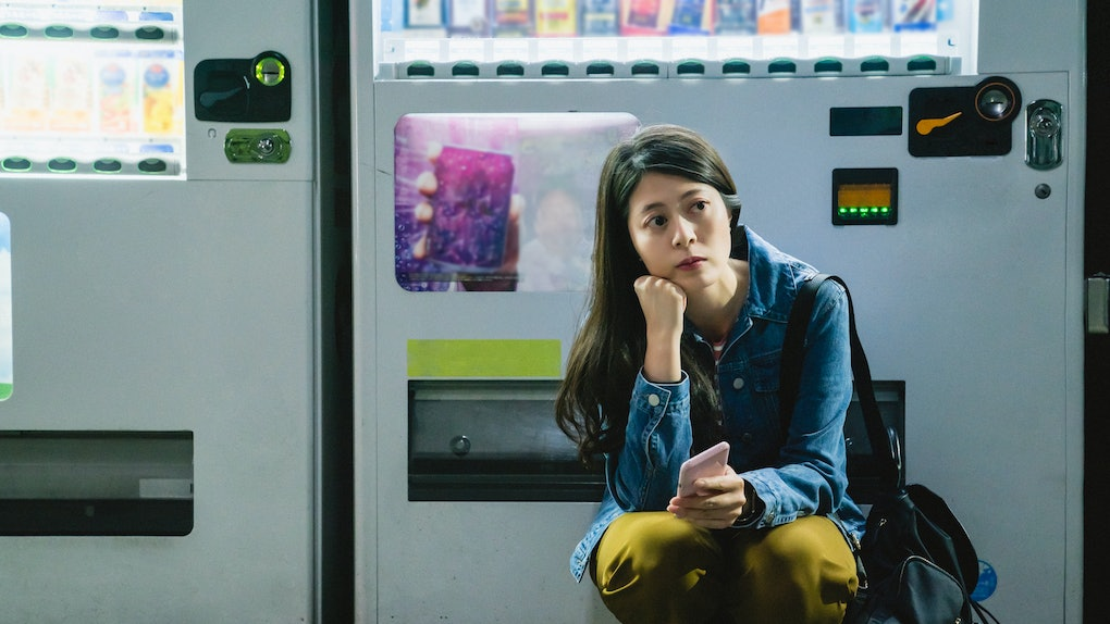asian girl squatting down and holding her phone to wait for something with a confused thinking and tired look.