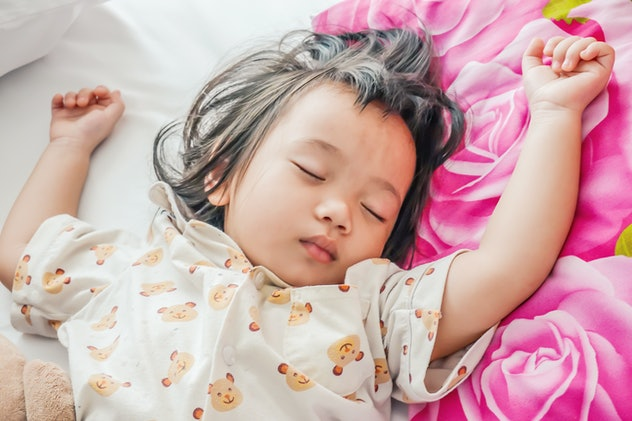Sleeping baby or infant girl on bed in bedroom with teddy bear in her arms.