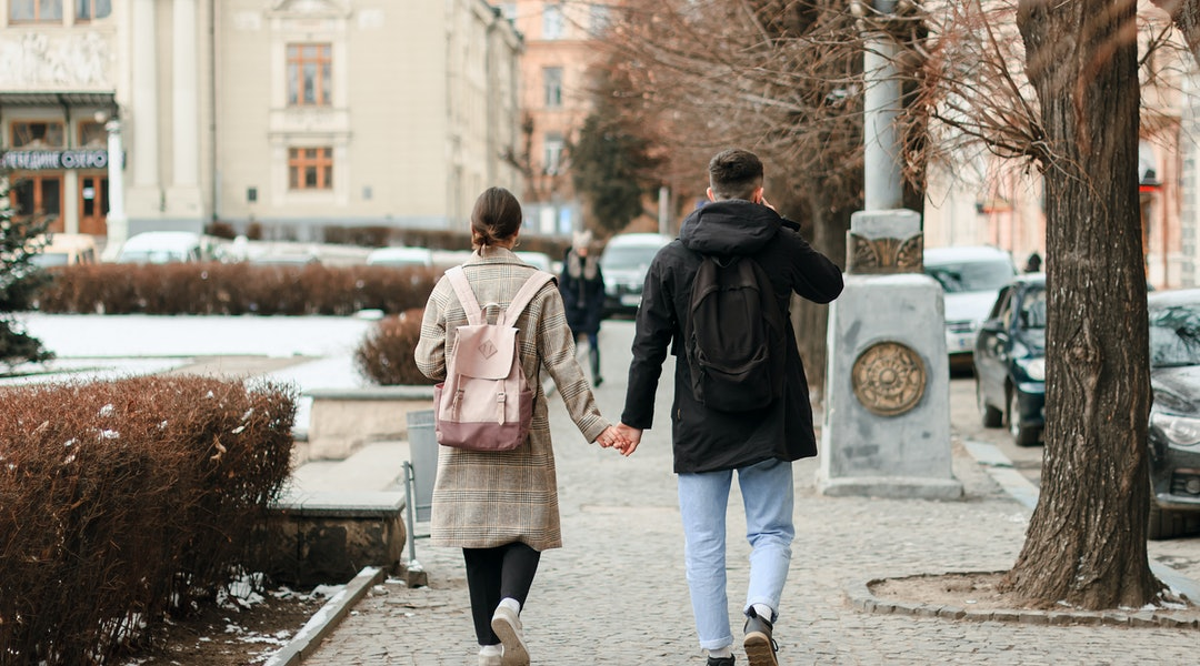 Wallking together. Full length of young couple on date having fun together. They are going hand in hand while enjoing winter holidays