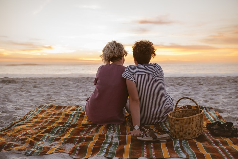 Rearview of a content young lesbian couple sitting together on a blanket at the beach watching a romantic sunset