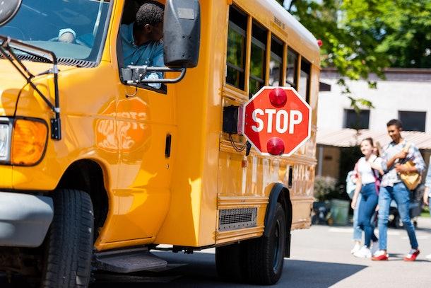 senior school bus driver looking at teens walking behind bus