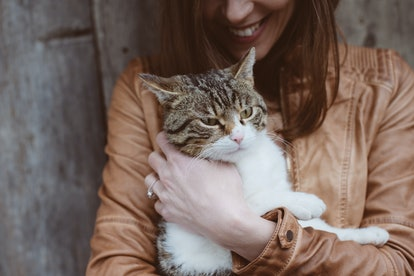 A brunette woman in a light brown leather jacket smiles while holding her cat.