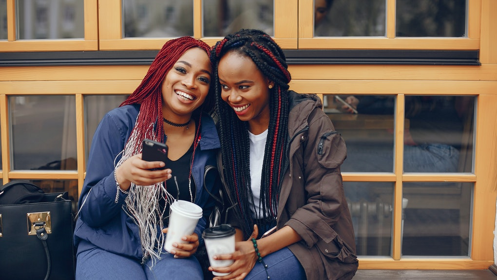 two beautiful and stylish dark-skinned girls with long hair sitting with coffee in a autumn city near building and drinking a coffee