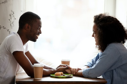 Happy multiracial couple holding hands, enjoying date in cafe, smiling African American boyfriend looking in eyes to attractive girlfriend, having pleasant conversation, spending time together