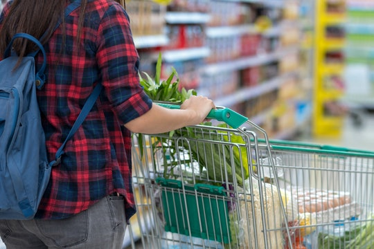 Closeup Young Asian women Hand holding the trolley for shopping over the store blurred in department store bokeh background