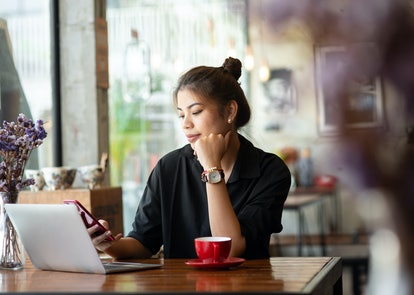 Asian woman working in cafe and using smart phone.