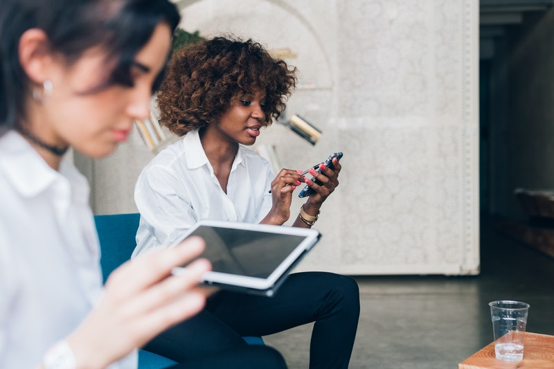 two multiracial young women working with digital device in modern office – freelance, interaction,  technology