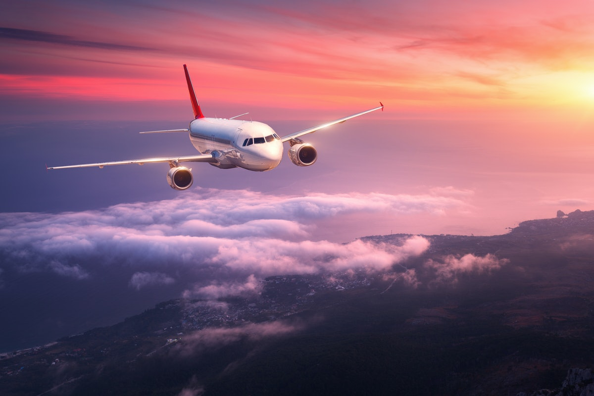 Passenger airplane. Landscape with big white airplane is flying in the red sky over the clouds and s...