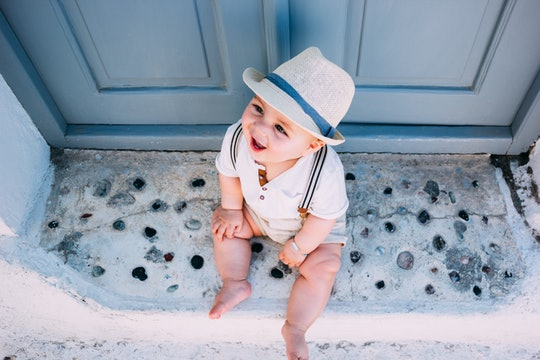 Beautiful baby sitting in front of a gray door in Santorini, Greece, wearing a hat