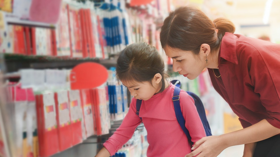 Back to school concept, Young asian mother or parent and little girl or pupil buying school supplies in store, Selective focus