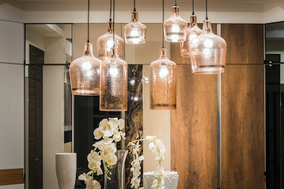Glass ceiling lamps with incandescent light bulbs in a living room with white ceiling and buildin closet