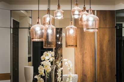 Glass ceiling lamps with incandescent light bulbs in a living room with white ceiling and buildin cl...