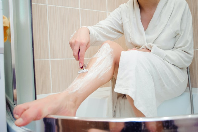Woman shaves her leg