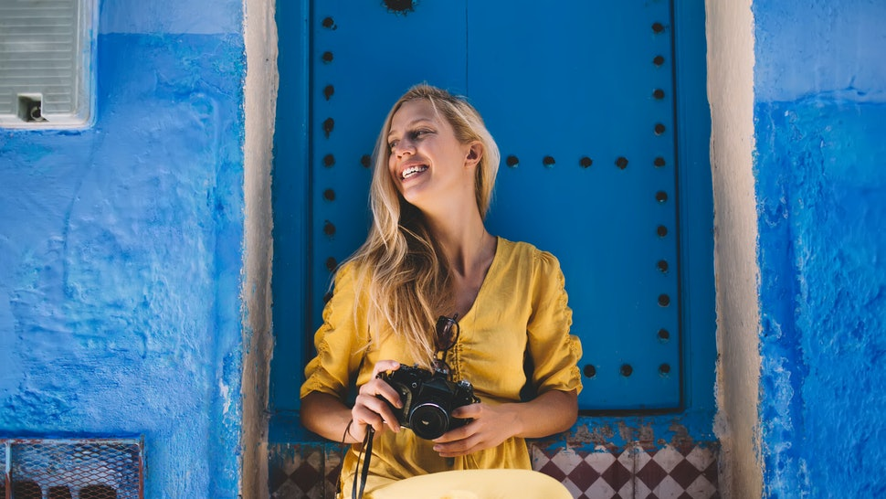 Excited female tourist with retro equipment in hands resting near oriental blue doors in Morocco and feeling happiness from summer berber vacations, happy woman enjoying discover trip to chaouen