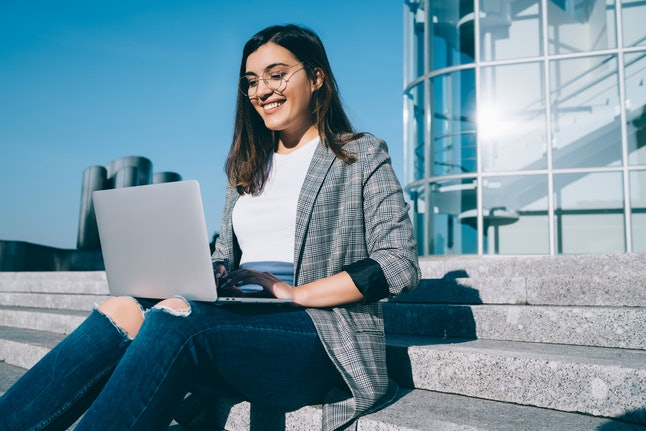 Pretty female student with cute smile keyboarding something on netbook while relaxing after lectures in University, cheerful happy woman working on laptop computer while sitting outdoors on stairs